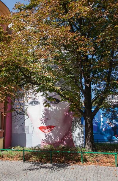 Kora by Bruno Althamer (2019) Honoring domestic rock goddess Kora – who lost her battle against cancer last year – this mural was painted as part of a wider action to commemorate the great women of Poland. The work has been intelligently positioned amid the trees so that the musician grows and loses her hair with the passing of each season. ul. Nowy Świat 18/20